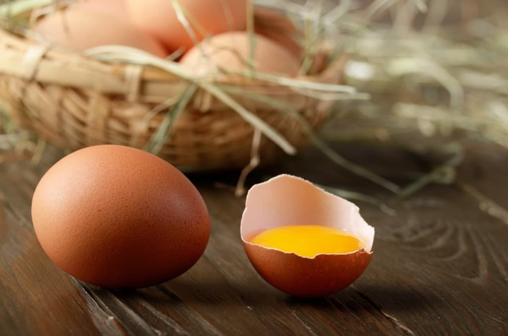 broken-egg-with-yolk-and-fresh-brown-organic-eggs-c7p2mnx.jpg